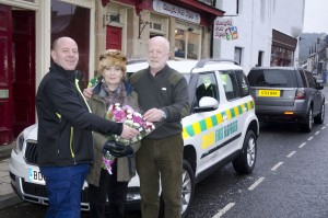 Comrie First Response manager Alan Moffat presents a bouquet of flowers to Lorna Ramsay. Lorna and David Ramsay of Kelvin TOP - SET have donated a new Skoda Yeti to the community charity